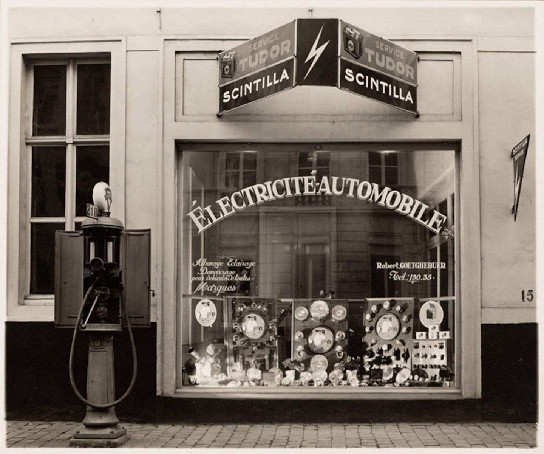Zicht op vitrine van winkel Robert Goetghebuer, verkoper van elektrische benodigdheden voor rijtuigen