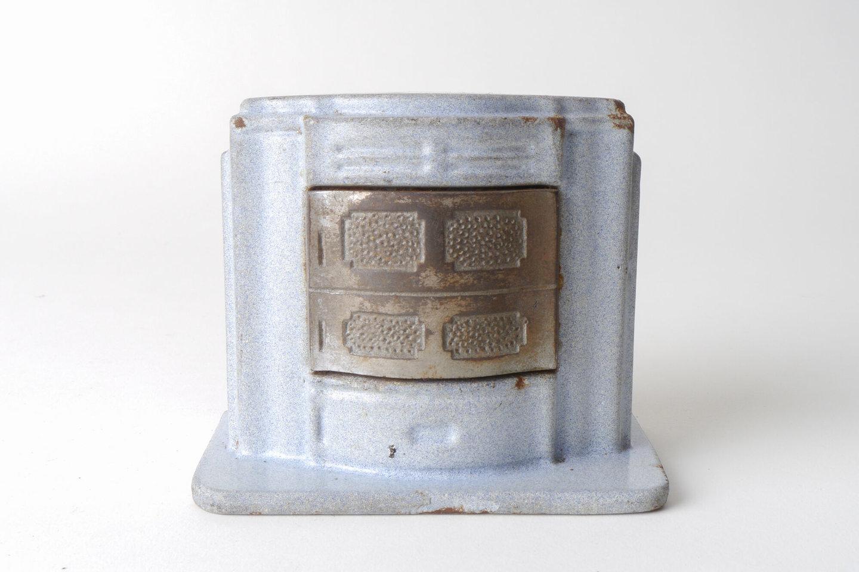 Geëmailleerde spaarpot in de vorm van een kachel van het merk Ciney