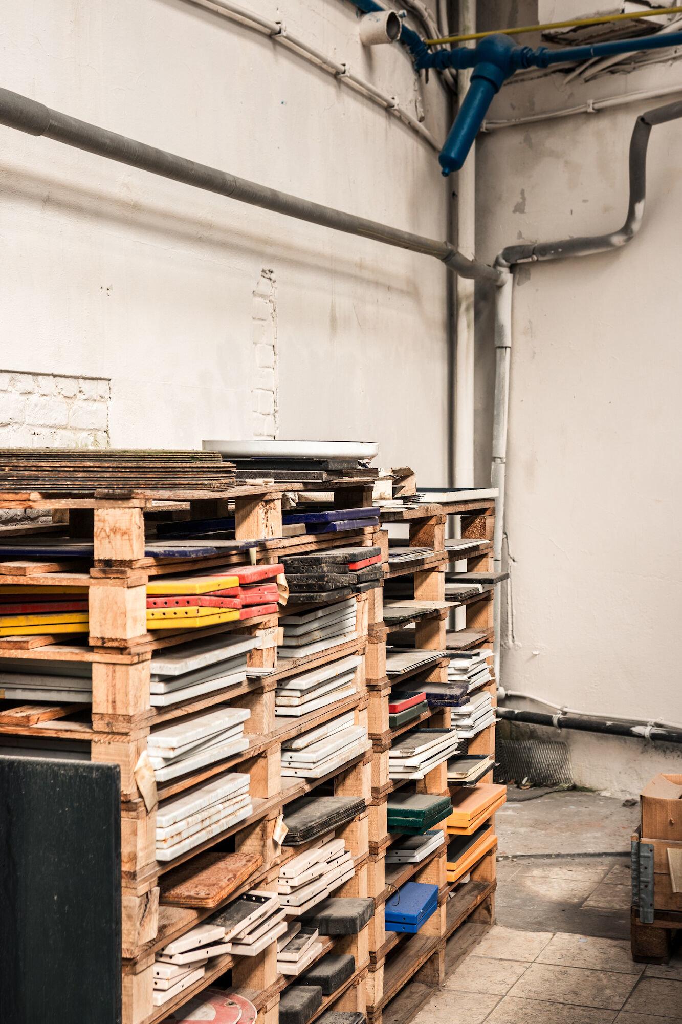 Magazijn met emailborden op rek in het atelier van Emaillerie Belge