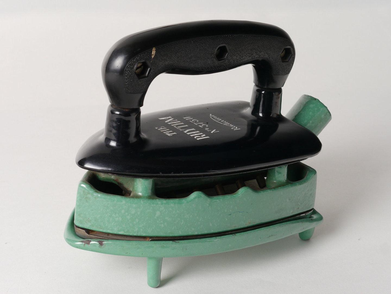 Geëmailleerd gasstrijkijzer en bijhorende treeft van het merk Radiation