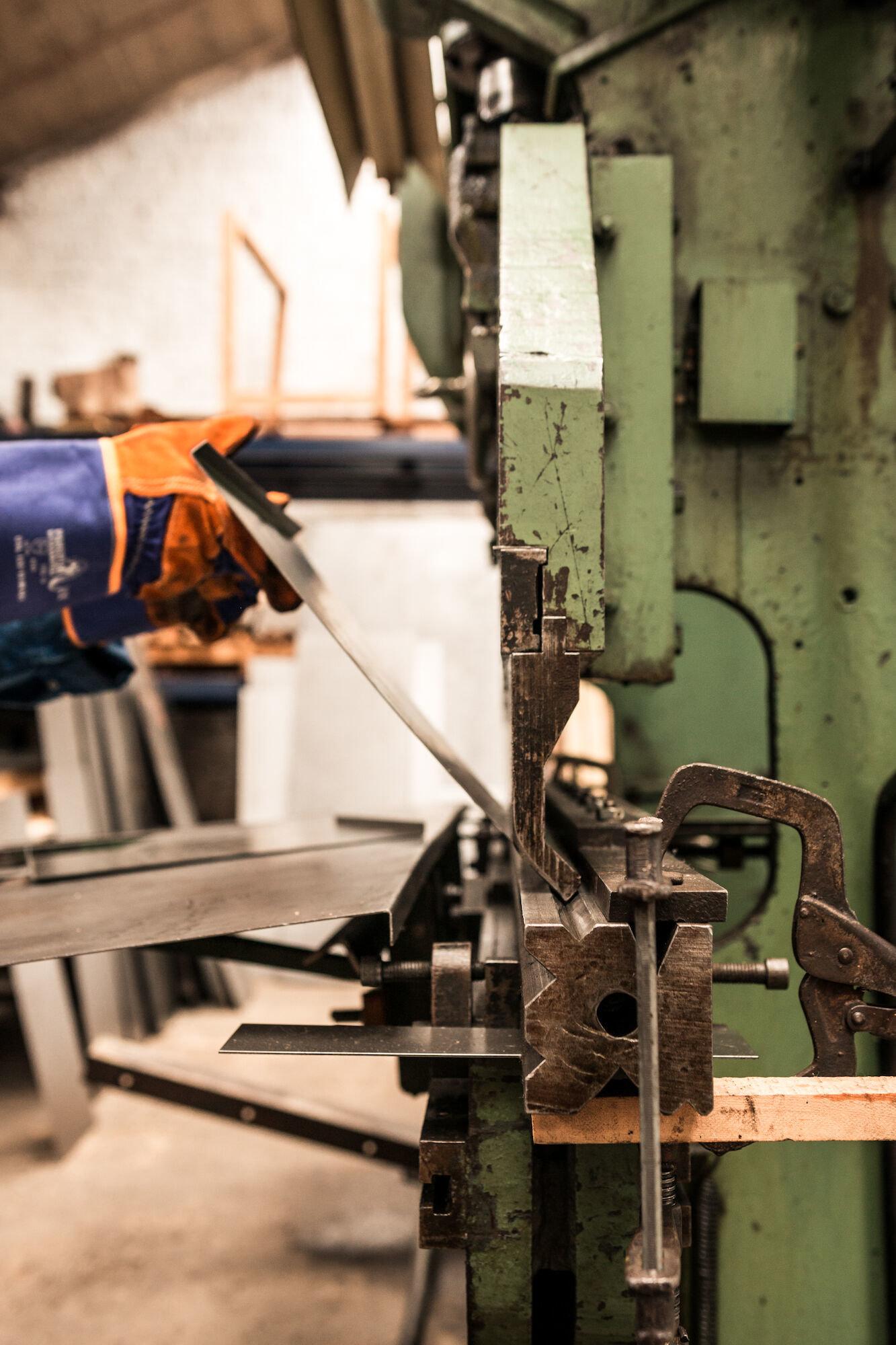 Plaatslager aan het werk in het atelier van Emaillerie Belge