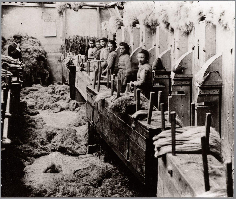 Jonge arbeidsters aan het werk in het zwingelkot van een vlasfabriek