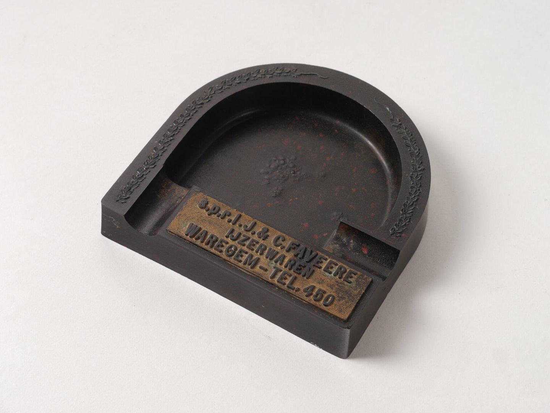 Hoefijzervormige asbak verspreid als reclame voor ijzerwaren Faveere