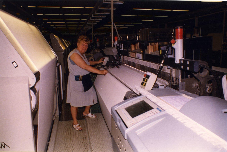 Arbeidster aan een weefmachine in UCO Braun in Gent